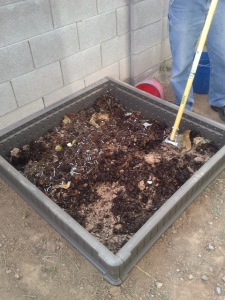 Compost being spread over dirt in a raised bed.